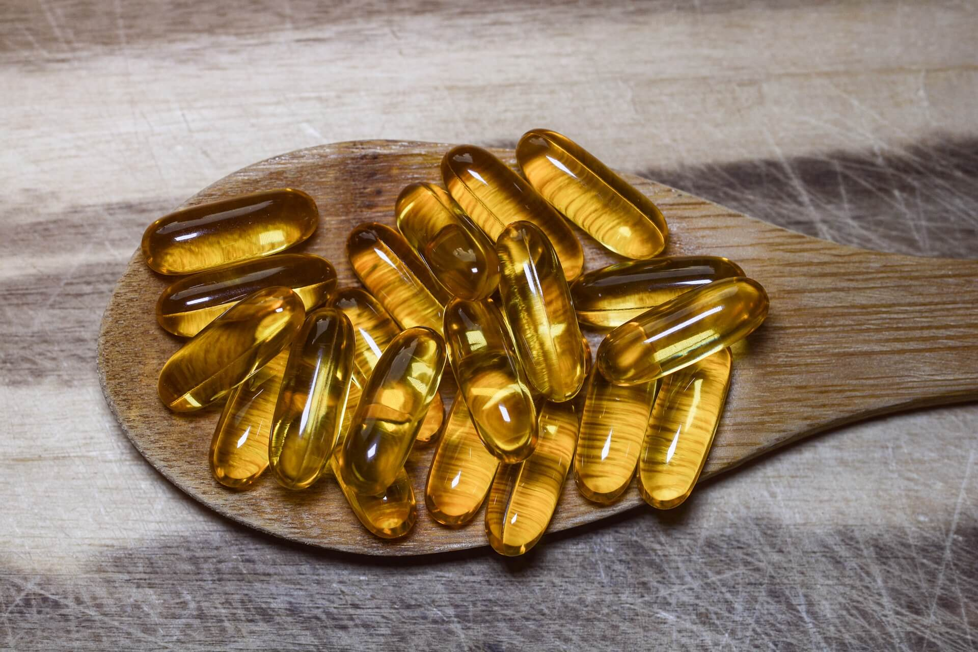vitamin supplements on wooden spoon